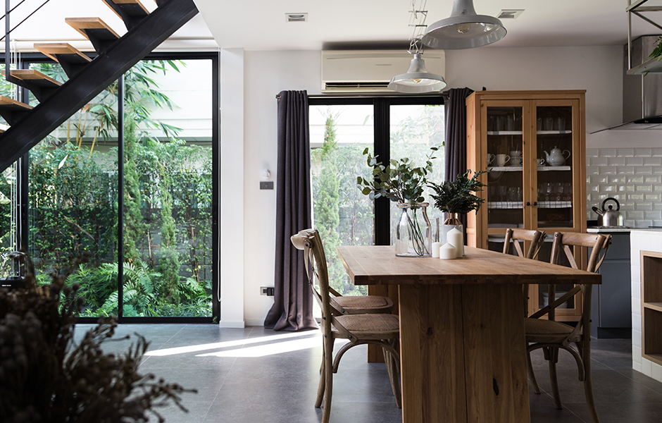 Kitchen interior with wood furniture, plants, and natural light