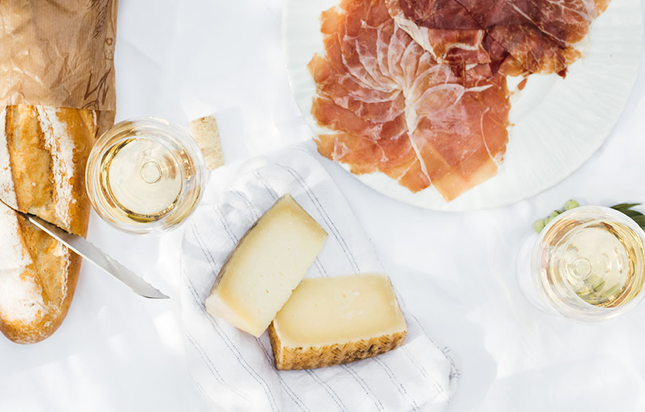 Overhead image of meat, cheese, and wine