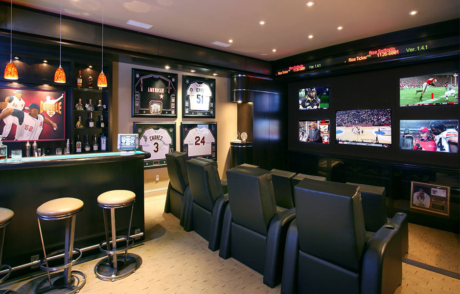 Sports themed man cave with memorabilia and multiple tv screens on the wall.
